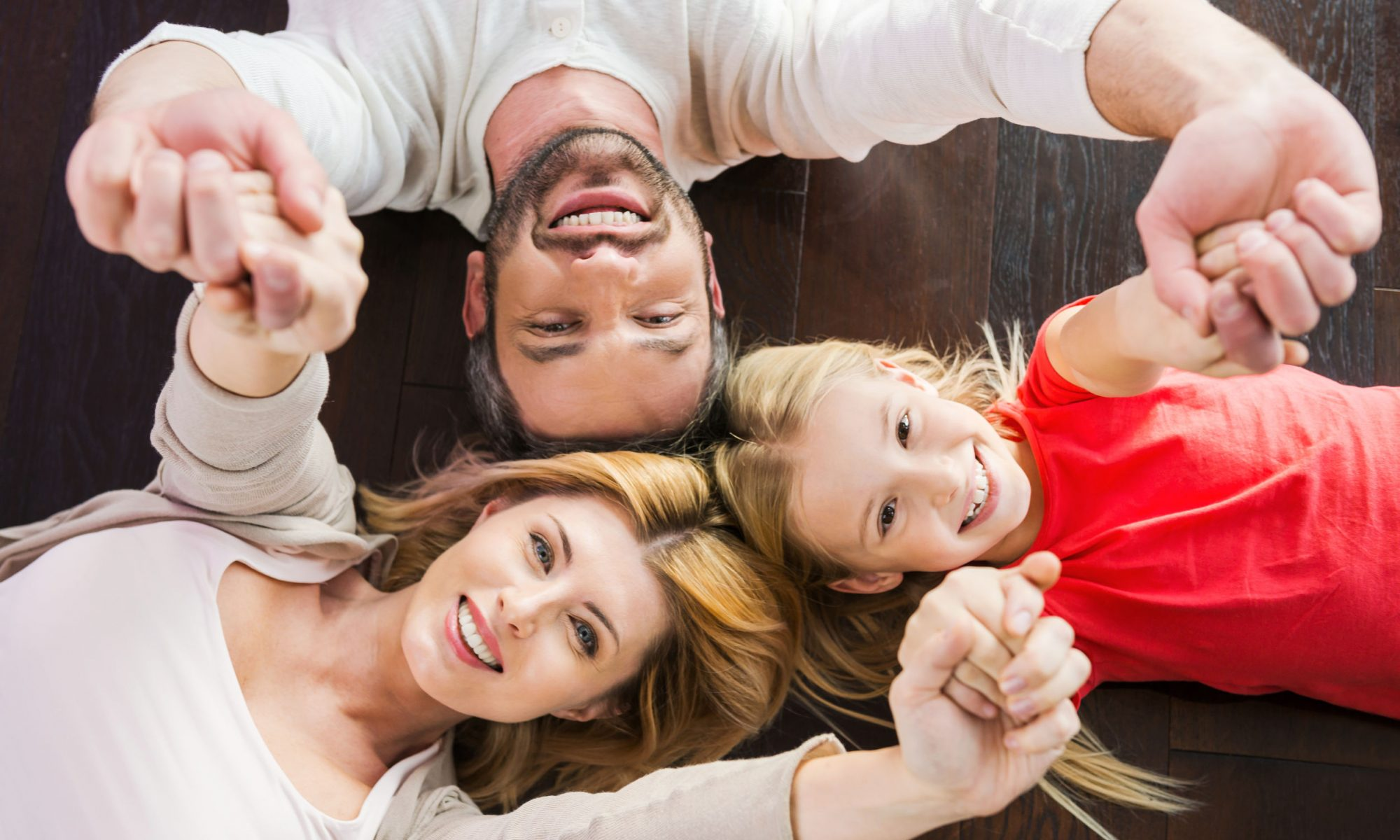 35294022 - happy family together. top view of happy family of three bonding to each other and smiling while lying on the hardwood floor
